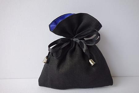 black drawstring purse on white surface