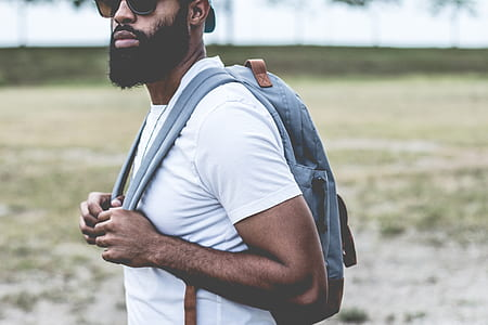 man wearing white crew-neck t-shirt and gray backpack