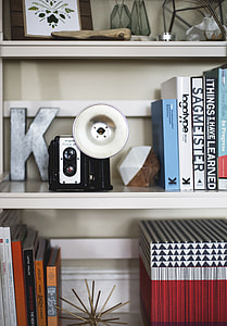 black and white instant camera on white wooden shelf