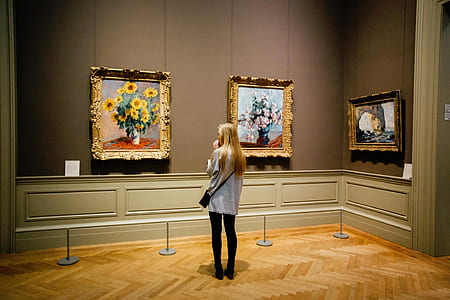 woman standing in front of three paintings