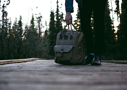 person carrying gray bag