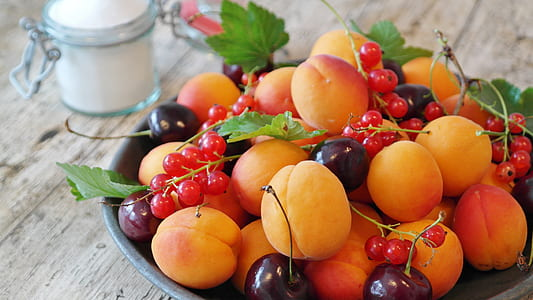 yellow and red cherry fruit on top of bowl
