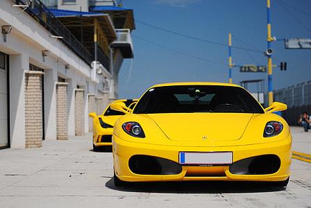 yellow Ferrari sports car on road during daytime