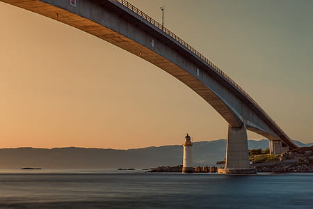 lighthouse under gray bridge during golden hour