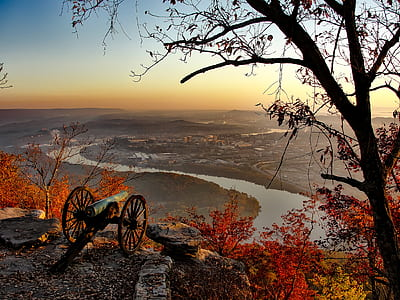 photo of black cannon on top of mountain facing city