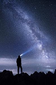 man using flashlight during night ime