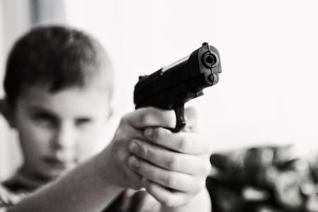 boy holding black semi-automatic pistol
