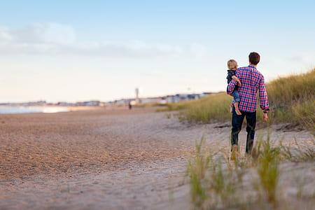 man carries boy walks on seashore at daytime