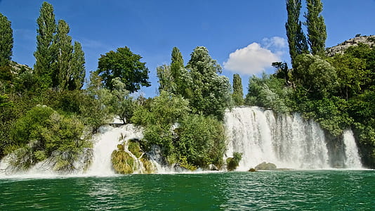 waterfalls and green trees under sunny sky