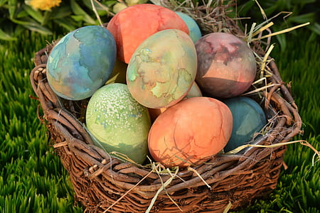 assorted-color Easter eggs on brown wicker basket