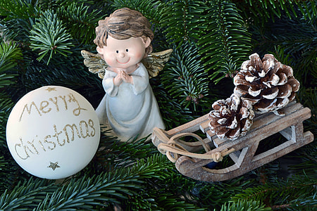 white Merry Christmas bauble beside angel figurine and brown sled