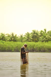 man standing in body of water while holding fishing net