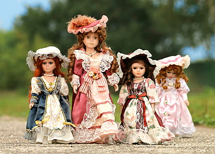 four female dolls in pink and blue dresses