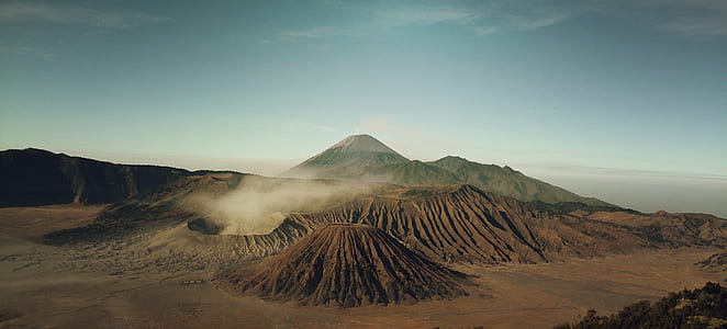 brown volcano under cloudy sky during daytime