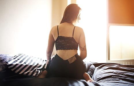 Women Wearing Black Floral Lace Bra and Black Denim Jeans Sitting on Black Sheet Bed Photo
