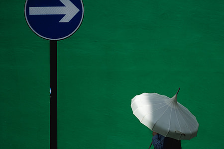man holding white umbrella nearly on road sign