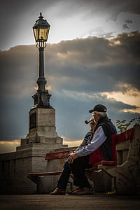 man and women sitting on bench during sunset