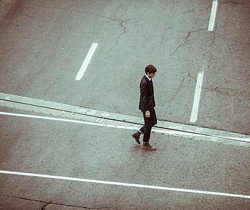man wearing brown boots walking on road