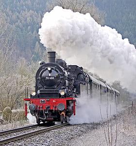 red and black train with smoke during daytim