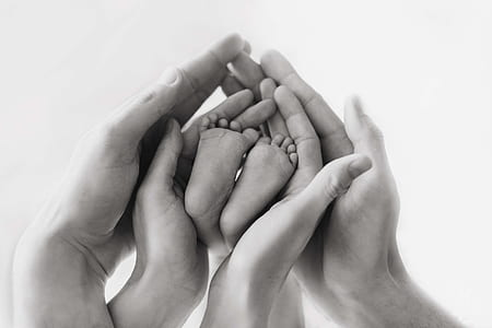 grayscale photo human hands and baby feet