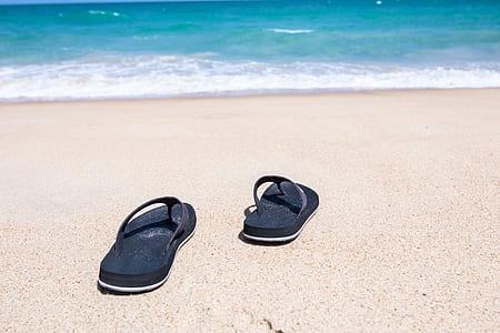 pair of black flip-flops on brown sand along seashore