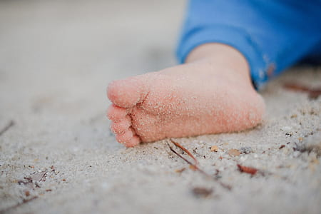 baby's right feet on sand