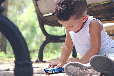 boy holding a blue die-cast vehicle model