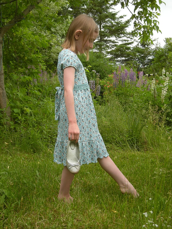 girl walking on lawn during day time