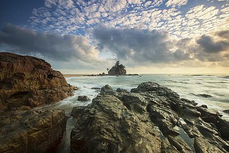 Brown Rocks on Seashore Under White Cloud Sky