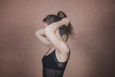 woman wearing black shirt holding hair