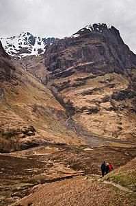 three people walking in hill pathway near snow mountain