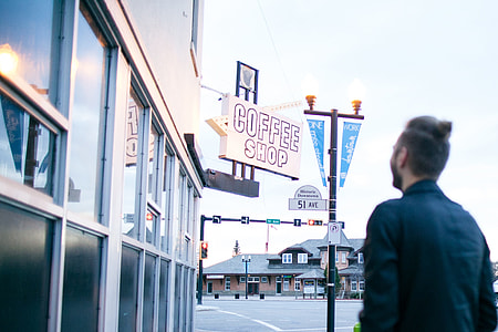man in black dress shirt standing outside coffee shop during daytime
