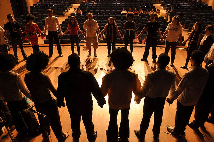 people holding hands forming circle on stage