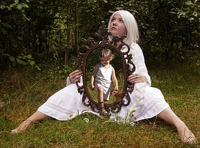 woman in white dress sitting on grass holding mirror