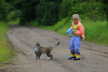 toddler wearing pink jacket standing near brown cat on road