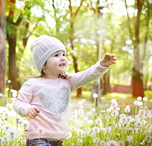 girl in pink shirt and gray knit hat near white flower plant