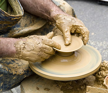 person shaping brown clay