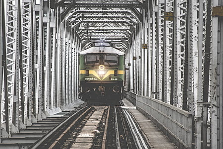 green and gray train near gray metal post at daytime