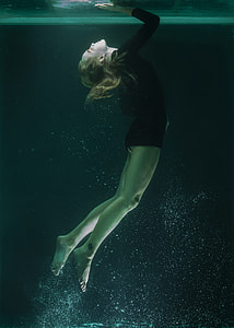 person under water wearing black wet suit