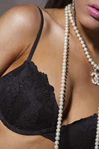 woman in beaded pearl necklace and black brassiere