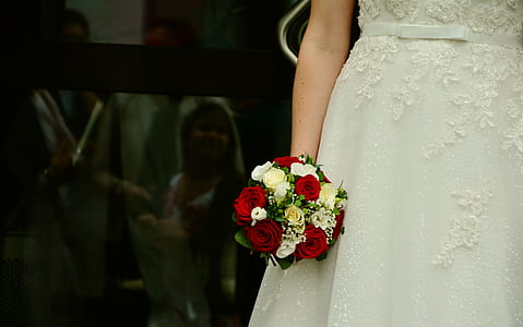 woman wearing white wedding dress holding rose flower bouquet