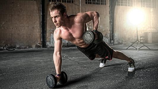 man doing push-up using dumbbells