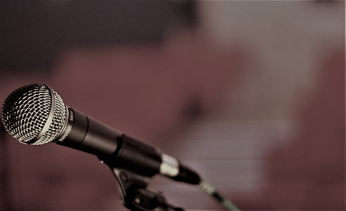 shallow focus photography of black microphone on holder