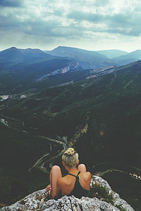 woman sitting on peak of a mountain with mountain view