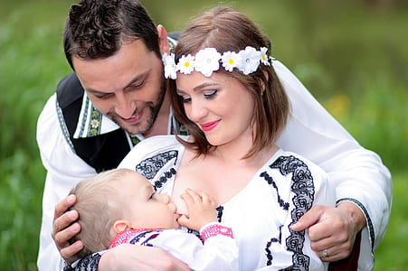 woman wearing flower headdress carrying baby at the back of man wearing white long-sleeved shirt