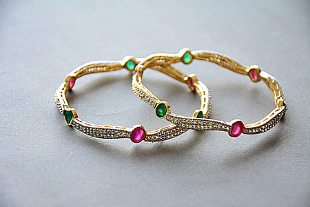 pair of gold-colored and gemstones studded bracelets