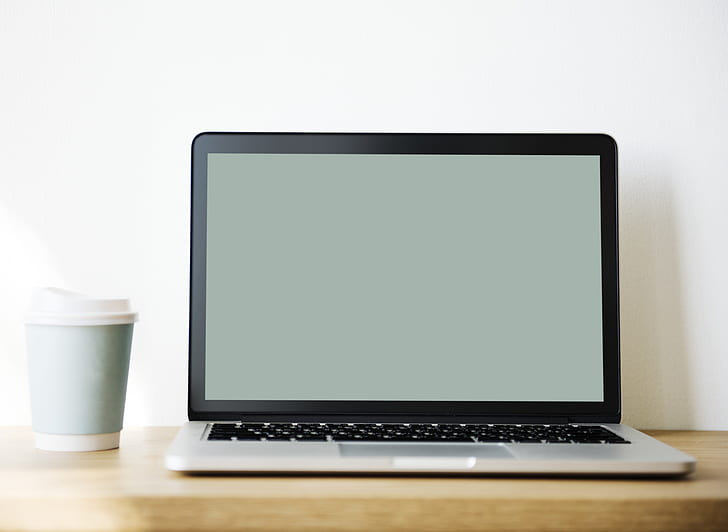 MacBook Pro beside travel mug