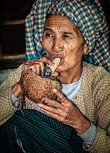 woman holding brown tobacco and brown coconut