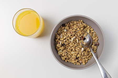 Overhead shot of a bowl of granola and a glass of fresh orange juice