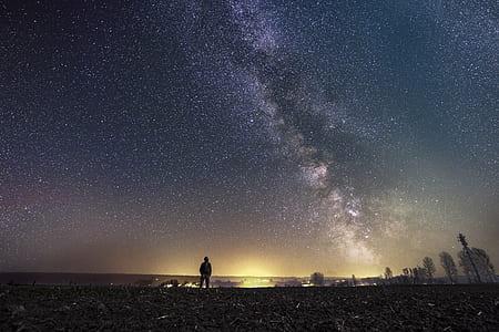 man on seashore under white stars nighttime